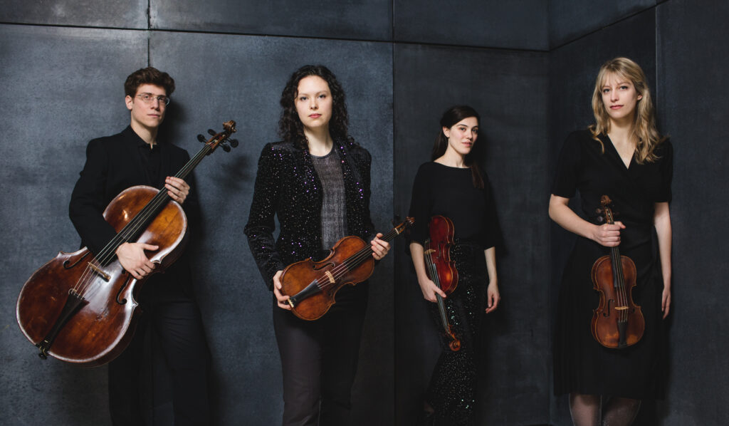 Four musicians (the Butter Quartet) holding their instruments against a slate grey backdrop. Two violins, a viola, and a cello.
