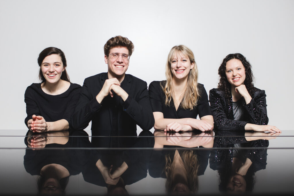 Four musicians sit at a reflective table smiling at the camera
