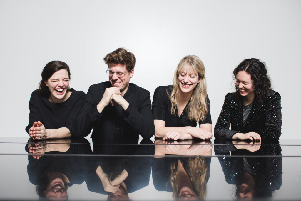 Four musicians sitting at a reflective table and laughing