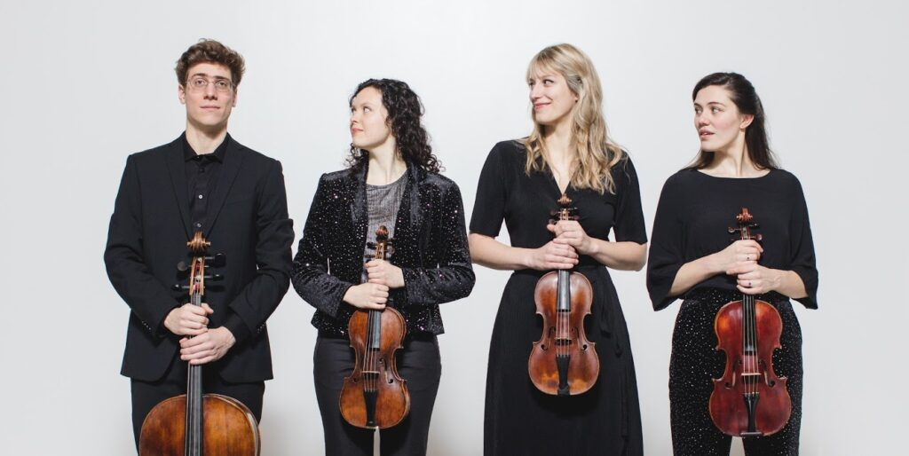 Four musicians standing in a row and holding their instruments. Chloe, Anna, and Isabel are all looking at Evan, who is looking at the camera